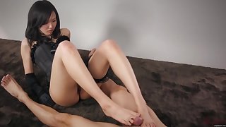 Slim brunette in black corset is giving a footjob to her lover and listening to his moans